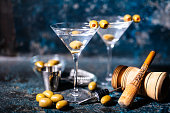 Martini cocktail drink with olives garnish and tools on rusty background
