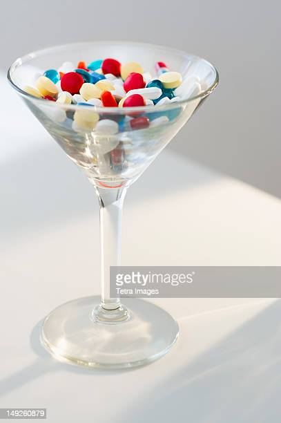 Martini glass filled with pills, studio shot