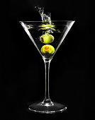 Splashing green olive in martini glass on black background