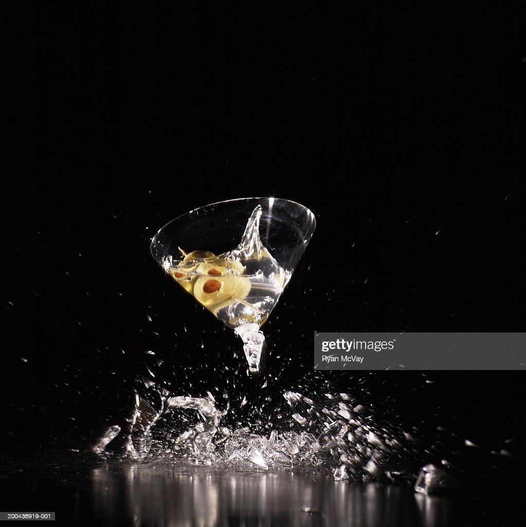 Martini glass shattering on floor (blurred motion) : Stock Photo