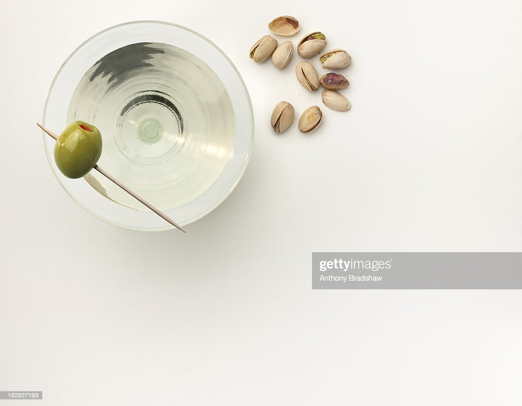 A martini with a stuffed olive and pistachio nuts