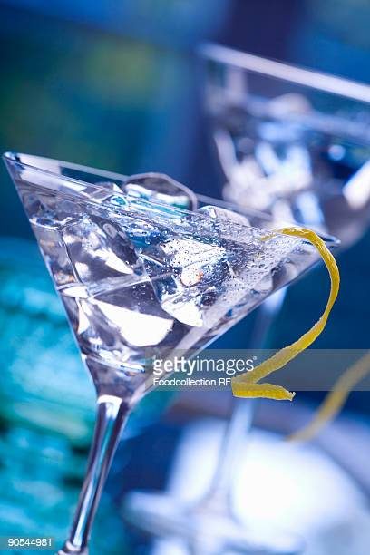 Martini with lemon peel and ice cubes, close up
