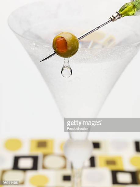 Martini with olive on cocktail stick, close-up
