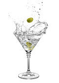 martini in glass with splashes and olives isolated on white background. Green olive is falling in the alcohol cocktail. Splash of martini from the falling olives