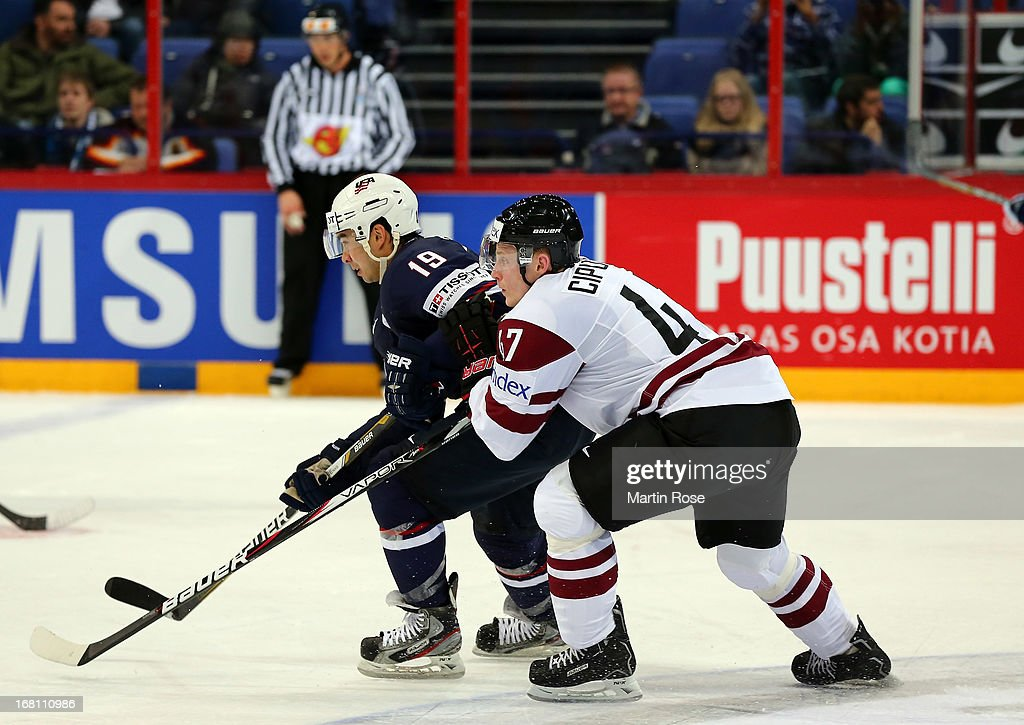 Martins Cipulis (R) of Latvia and Tim Stapleton (L) of USA battle for the puck during the IIHF World Championship group H match between Latvia and USA at Hartwall Areena on May 5, 2013 in Helsinki, Finland.