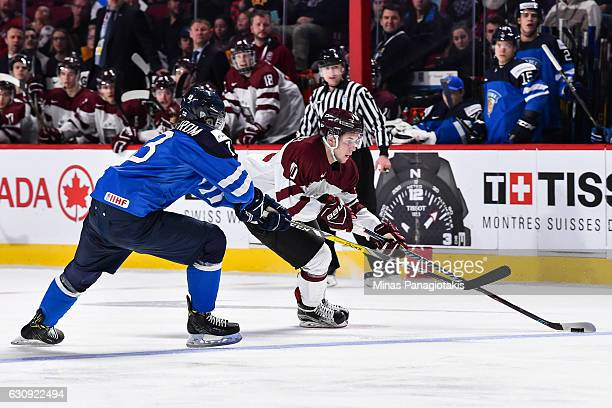 Martins Dzierkals of Team Latvia skates the puck against Henrik Borgstrom of Team Finland during the 2017 IIHF World Junior Championship relegation...