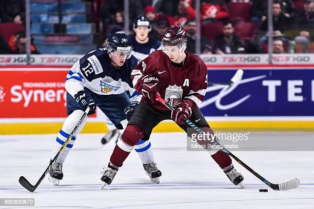 Martins Dzierkals of Team Latvia skates the puck against Juuso Valimaki of Team Finland during the 2017 IIHF World Junior Championship relegation...
