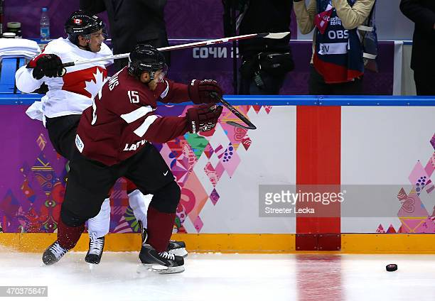 Martins Karsums of Latvia checks Chris Kunitz of Canada into the boards during the Men's Ice Hockey Quarterfinal Playoff on Day 12 of the 2014 Sochi...