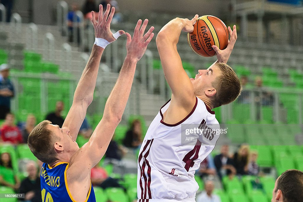 Martins Meiers (R) of Latvia vies with Maxym Korniyenko of Ukraine during the FIBA EuroBasket second round Group E basketball championship qualification match between Latvia and Ukrainem, in Ljubljana, Slovenia, on September 11, 2013. AFP PHOTO / Jure Makovec