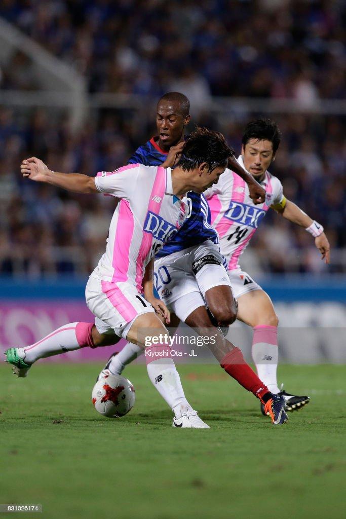 Martinus (C) of Yokohama F.Marinos competes for the ball against Jung Seung Hyun (L) and Yoshiki Takahashi (R) of Sagan Tosu during the J.League J1 match between Yokohama F.Marinos and Sagan Tosu at Nippatsu Mitsuzawa Stadium on August 13, 2017 in Yokohama, Kanagawa, Japan.