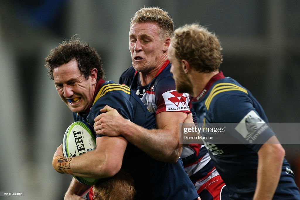 Marty Banks (L) of the Highlanders tries to break the tackle of Mitch Inman of the Rebels during the round six Super Rugby match between the Highlanders and the Rebels at Forsyth Barr Stadium on March 31, 2017 in Dunedin, New Zealand.