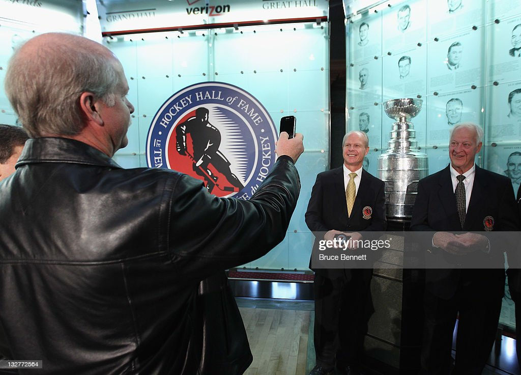 Marty Howe (L) takes a photo of his brother and father, 2011 Hall of Fame inductee Mark Howe and hockey legend <a gi-track='captionPersonalityLinkClicked' href=/galleries/search?phrase=Gordie+Howe&family=editorial&specificpeople=677316 ng-click='$event.stopPropagation()'>Gordie Howe</a> during a photo opportunity at the Hockey Hall Of Fame on November 14, 2011 in Toronto, Ontario, Canada.