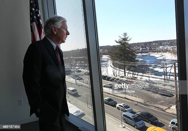Marty Meehan Chancellor of UMass Lowell looks out from fourth floor window of the new University Crossing building where he can see the Merrimack...