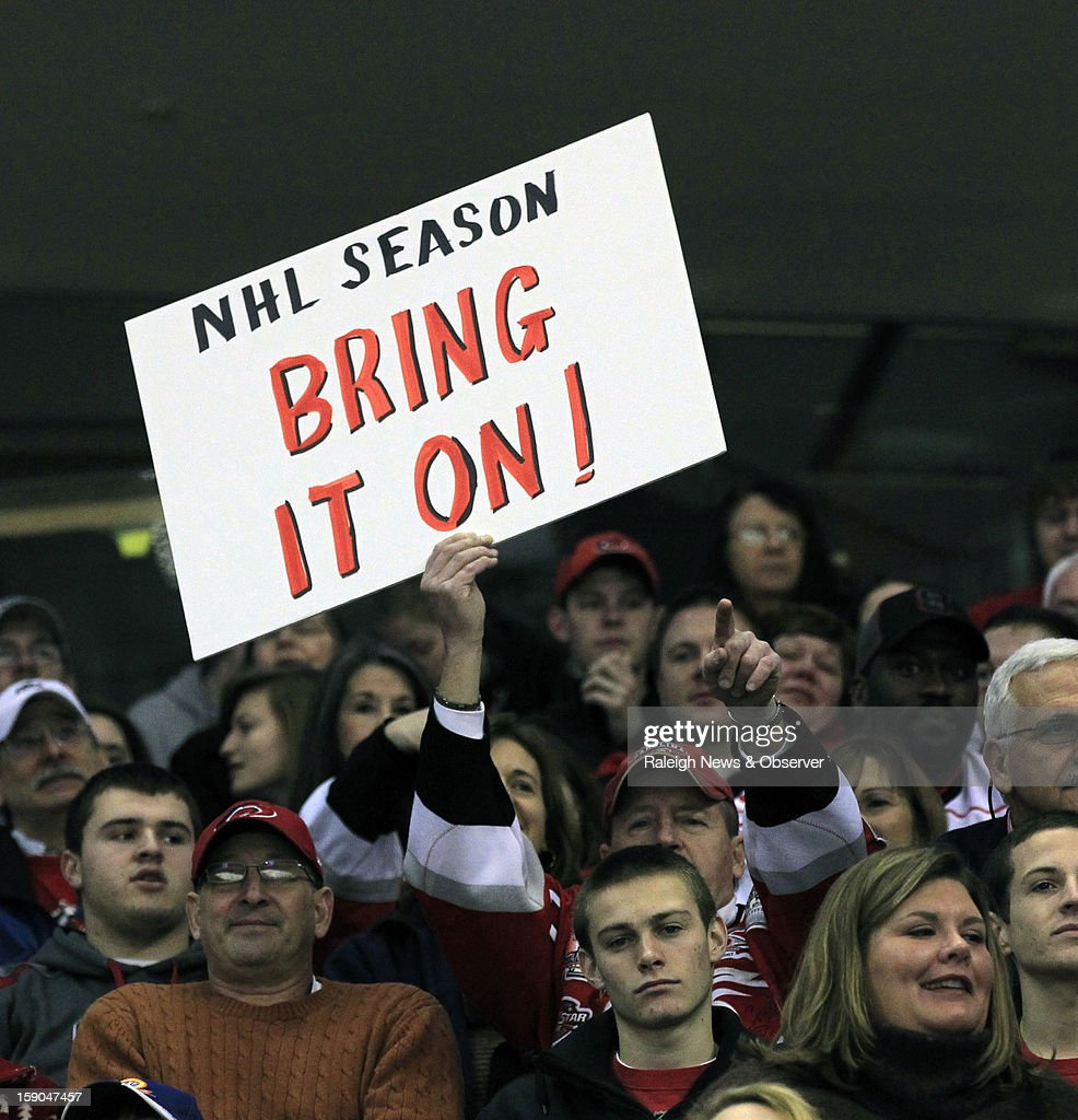 Marty Miller holds up his sign voicing his opinion on the NHL lockout as the Charlotte Checkers play the Norfolk Admirals in an American Hockey League game at the PNC Arena on Sunday, January 6, 2013, in Raleigh, North Carolina. The Checkers are the Carolina Hurricanes highest-level minor league franchise. The NHL announced an agreement with the players union on the lockout Sunday. 'It's about time' Miler said of the end of the lockout.