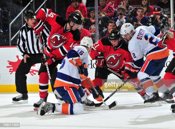Marty Reasoner and Mark Streit of the New York Islanders go for the puck against Adam Henrique and Andrei Loktionov of the New Jersey Devils at the...