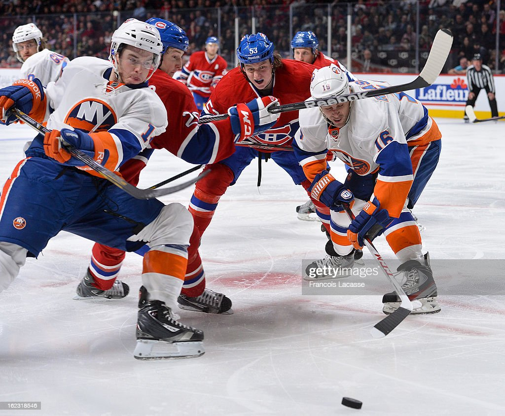 Marty Reasoner and Thomas Hickey of the New York Islanders battle for the puck with Ryan White of the Montreal Canadiens during the NHL game on...