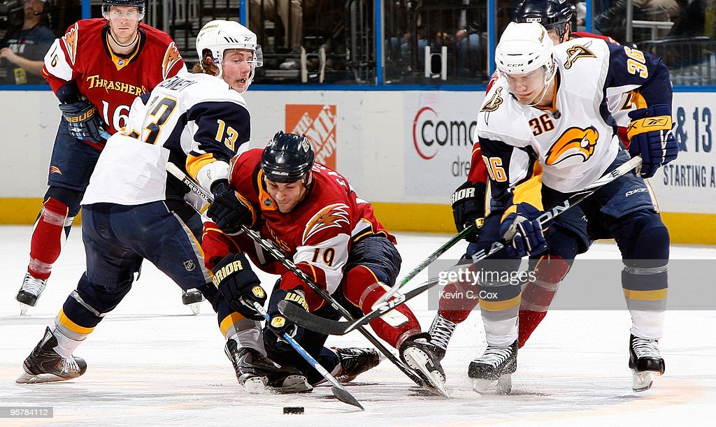 Marty Reasoner of the Atlanta Thrashers battles for the puck against Tim Kennedy and Patrick Kaleta of the Buffalo Sabres at Philips Arena on January...