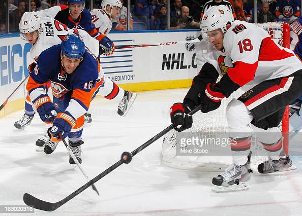Marty Reasoner of the New York Islanders and Jim O'Brien of the Ottawa Senators lunge for the puck at Nassau Veterans Memorial Coliseum on March 3...
