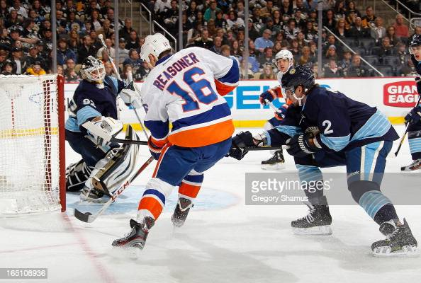 Marty Reasoner of the New York Islanders attempts a shot between Tomas Vokoun and Matt Niskanen of the Pittsburgh Penguins on March 30 2013 at Consol...