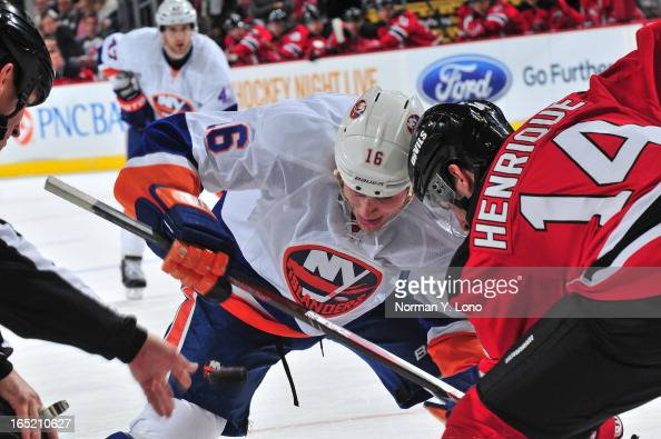 Marty Reasoner of the New York Islanders battles Adam Henrique of the New Jersey Devils at the face at the Prudential Center on April 1 2013 in...