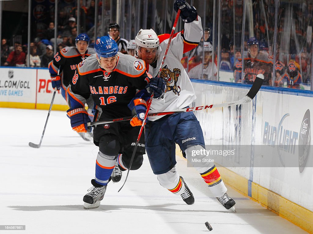 Marty Reasoner of the New York Islanders battles for the puck with Drew Shore of the Florida Panthers at Nassau Veterans Memorial Coliseum on March...