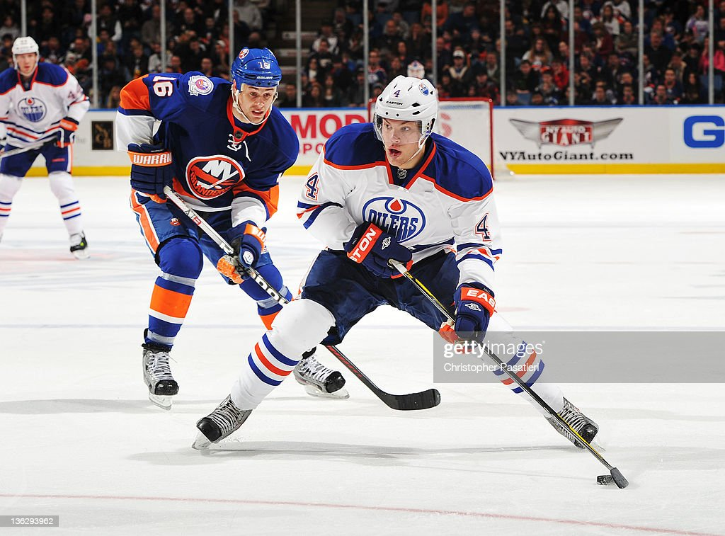 Marty Reasoner #16 of the New York Islanders heads for a shooting Taylor Hall #4 of the Edmonton Oilers at Nassau Veterans Memorial Coliseum on December 31, 2011 in Uniondale, New York.