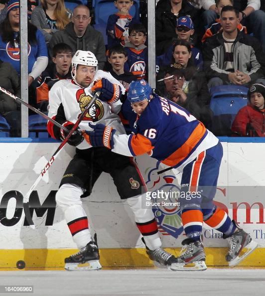 Marty Reasoner of the New York Islanders hits Chris Phillips of the Ottawa Senators along the boards at the Nassau Veterans Memorial Coliseum on...