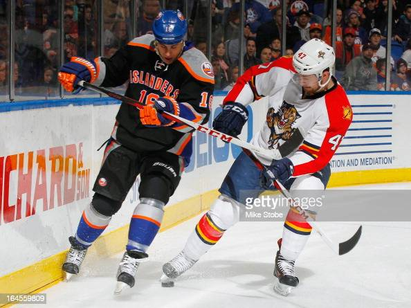 Marty Reasoner of the New York Islanders pursues the puck against Colby Robak of the Florida Panthers at Nassau Veterans Memorial Coliseum on March...