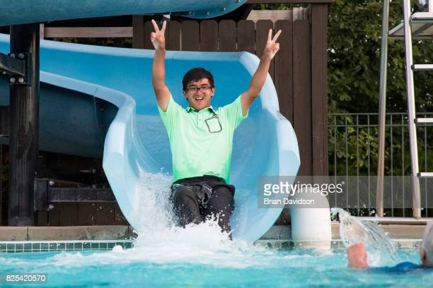 Marty Zecheng Dou celebrates by taking a water slide into a pool after winning the Digital Ally Open of the WEBCOM Tour at Nicklaus Golf Club at...