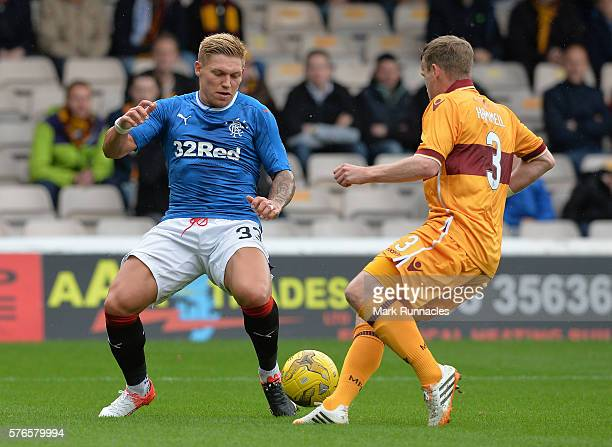 Martyn Waghorn of Rangers is tackled by Carl McHugh of Motherwell during the Scottish League Cup First Round Group Stage match between Motherwell FC...