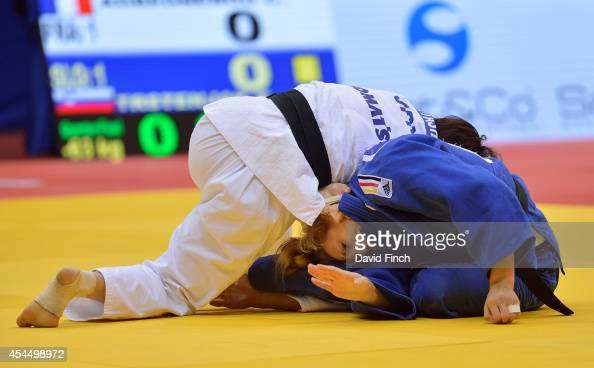 Martyna Trajdos of Germany taps frantically to submit as Miku Tashiro of Japan applies a strangle to win their team contest by an ippon during the...