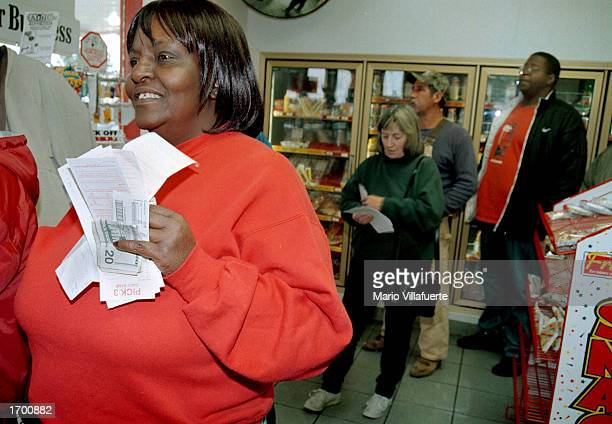 Marva Phillips of Dallas Texas waits patiently with a handful of Power Ball tickets and money at the Derrick Truck Stop December 24 2002 in Greenwood...