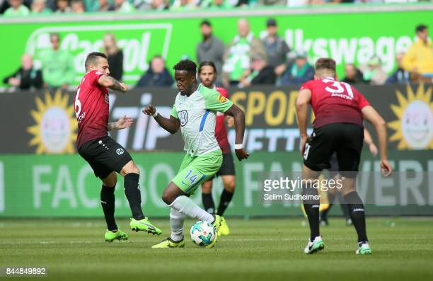 Marvin Bakalorz and Waldemar Anton of Hannover 96 fights for the ball with Divock Origi of VfL Wolfsburg during the Bundesliga match between VfL...