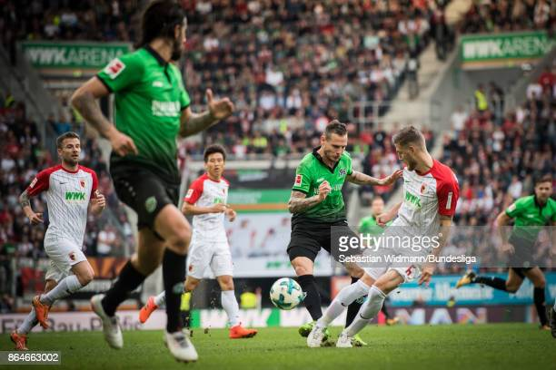 Marvin Bakalorz of Hannover 96 and Jeffrey Gouweleeuw of Hannover 96 compete for the ball during the Bundesliga match between FC Augsburg and...
