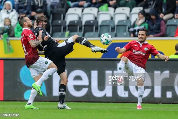 Marvin Bakalorz of Hannover Julian Korb of Hannover and Christoph Kramer of Moenchengladbach battle for the ball during the Bundesliga match between...
