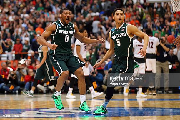 Marvin Clark Jr #0 and Bryn Forbes of the Michigan State Spartans celebrate defeating the Louisville Cardinals 76 to 70 in overtime of the East...