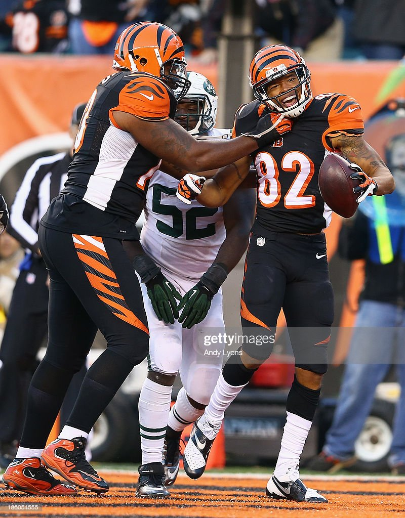 Marvin Jones #82 of the Cincinnati Bengals celebrates with Anthony Collins #73 (left) after scoring a touchdown during the NFL game against the New York Jets at Paul Brown Stadium on October 27, 2013 in Cincinnati, Ohio.