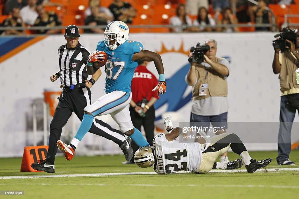 Marvin McNutt #87 of the Miami Dolphins runs 56 yards for a touchdown past Corey White #24 of the New Orleans Saints with four minutes remaining during a preseason game on August 29, 2013 at Sun Life Stadium in Miami Gardens, Florida. The Dolphins defeated the Saints 24-21.