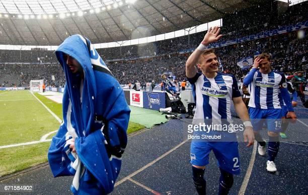 Marvin Plattenhardt of Hertha BSC protect himself against hail under the cover during his team mates Peter Pekarik and Sebastian Langkamp of Hertha...