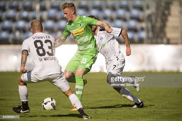 Marvin Schulz of Borussia Moenchengladbach challenges Ali Ibrahimaj of SV Waldhof Mannheim during the friendly match between SV Waldhof Mannheim and...