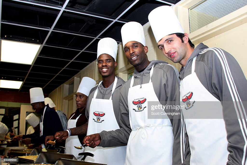 Marvin Williams, Joe Smith, and Zaza Pachulia (L-R) of the Atlanta Hawks smile for a photo during the Hawks Thanksgiving Event at Gateway Center on November 24, 2009 in Atlanta, Georgia.