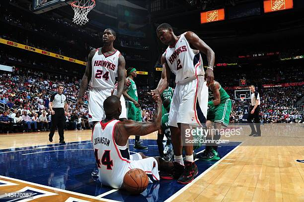 Marvin Williams of the Atlanta Hawks and Joe Johnson of the Atlanta Hawks help Ivan Johnson of the Atlanta Hawks from the floor in Game Two of the...