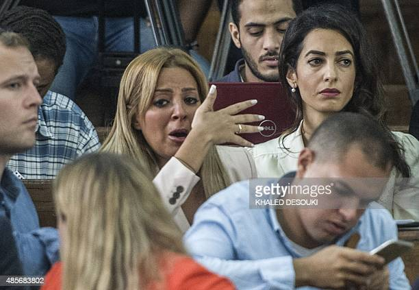 Marwa Fahmy the wife of Canadian AlJazeera journalist Mohamed Fahmy reacts as she sits next to Amal Clooney the human rights lawyer representing...