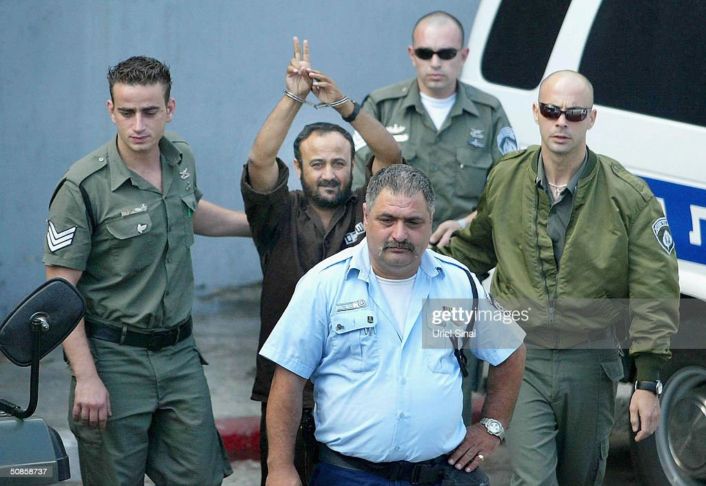 Marwan Barghoutti, head of the Palestinian Fatah Tanzim and Al-Aqsa Martyrs' Brigades, gestures as he is brought by Israeli police to the Tel Aviv District Court for the judicial ruling in his trial on May 20, 2004 in Tel Aviv, Israel. Israel charged Barghoutti with involvement in the murder of Israelis, leading Palestinian militants in terror attacks against dozens of Israeli targets since the outbreak of the intifada.