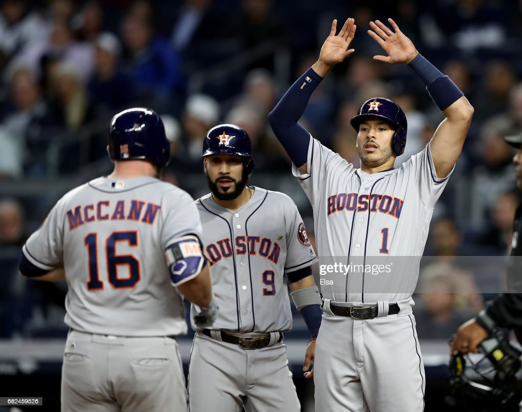 Marwin Gonzalez #9 and Carlos Correa #1 of the Houston Astros congratulate teammate Brian McCann #16 after McCann drove them all home with a home run in the fourth inning against the New York Yankees on May 12, 2017 at Yankee Stadium in the Bronx borough of New York City.
