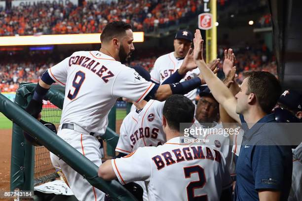 Marwin Gonzalez of the Houston Astros celebrates with teammates after scoring on a sacrifice fly by Alex Bregman during the second inning against the...