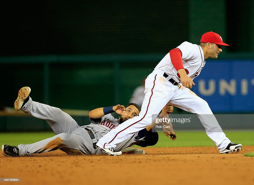 Marwin Gonzalez of the Houston Astros grabs the wrist of second baseman Danny Espinosa of the Washington Nationals after being forced out during the...