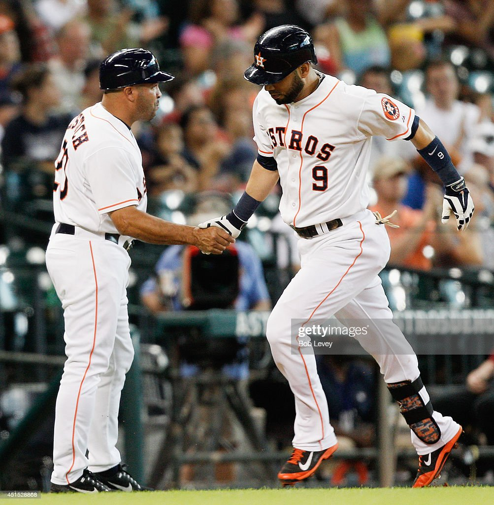 Marwin Gonzalez #9 of the Houston Astros hits a home run in the second inning as he receives congratulations from Pat Listach at Minute Maid Park on June 30, 2014 in Houston, Texas.
