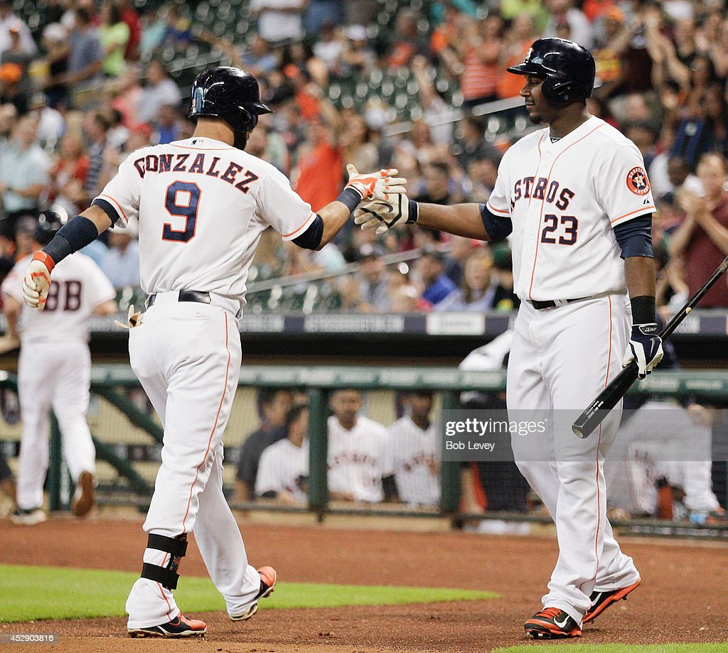 Marwin Gonzalez of the Houston Astros is congratulated by Chris Carter after hitting a home run in the first inning against the Oakland Athletics at...