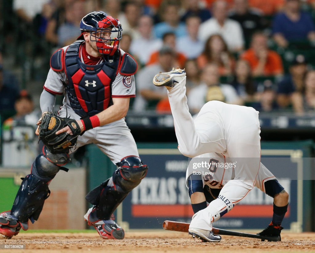 Marwin Gonzalez #9 of the Houston Astros loses hjis balance as he avoids a pitch in the eighth inning as Matt Wieters #32 of the Washington Nationals looks on at Minute Maid Park on August 22, 2017 in Houston, Texas.